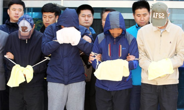 Crewmembers of the sunken ferry Sewol, including the chief engineer, two chief mates and a second mate, stand in front of reporters after being questioned during a judge's review of prosecutors' request for arrest warrants for abandoning passengers, at the Mokpo branch of the Gwangju District Court, Tuesday. / Yonhap