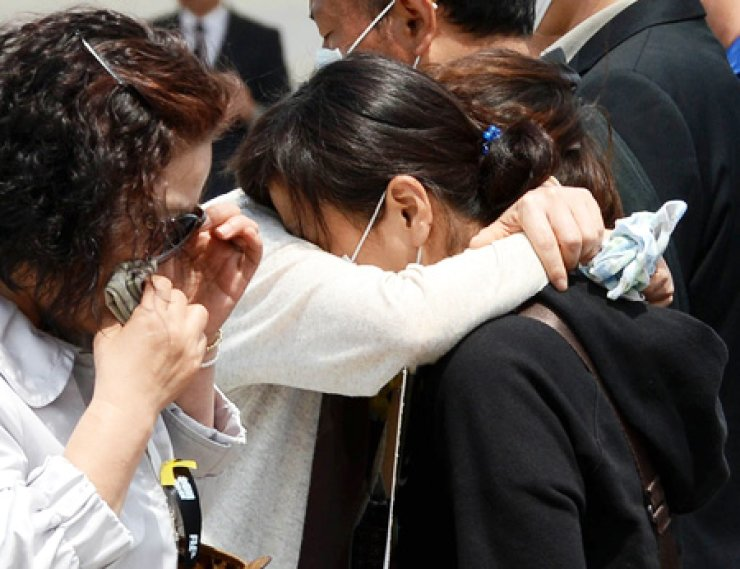 A mourner gives a big hug to one of the victimized family members of last month's ferry Sewol disaster while visiting the memorial altar set up in Ansan, Gyeonggi Province, Wednesday. Bereaved family members are currently staging a silent protest at the altar in request for a thorough investigation into the sinking of Sewol. / Korea Times photo by Hong In-ki