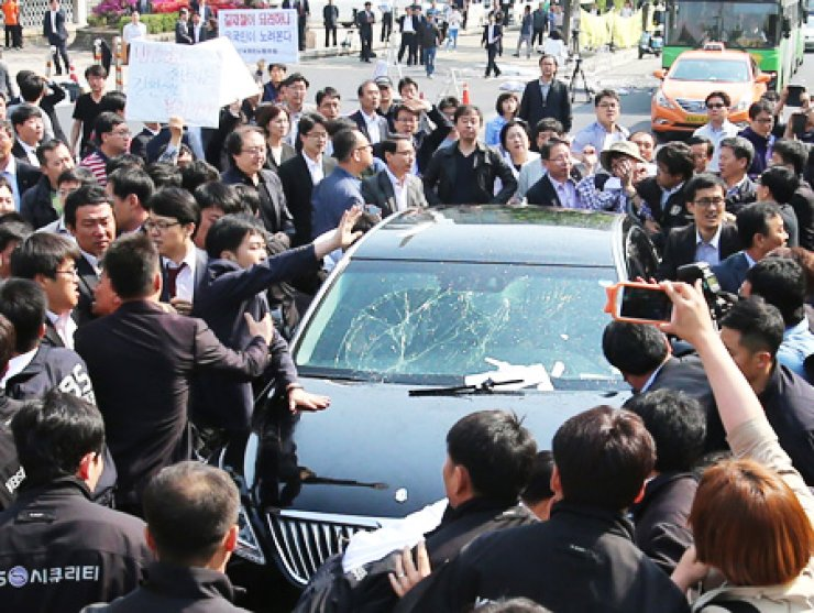 A sedan carrying KBS President Gil Hwang-young is surrounded by unionists and security guards at the state-run broadcaster's headquarters in Yeouido, Monday. Union members blocked Gil, who they claim is a government stooge, from going to the office, and demanded his resignation. The vehicle's windshield was cracked during the physical confrontation between KBS security guards and union members. / Yonhap