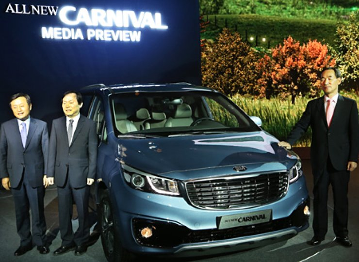 Kia Motors President Lee Sam-ung, right, Executive Vice Presidents Kim Chang-sik, left, and Yoon Seon-ho, stand next to the new Carnival during an unveiling event at Walkerhill Hotel in Seoul, Thursday./ Courtesy of Kia Motors