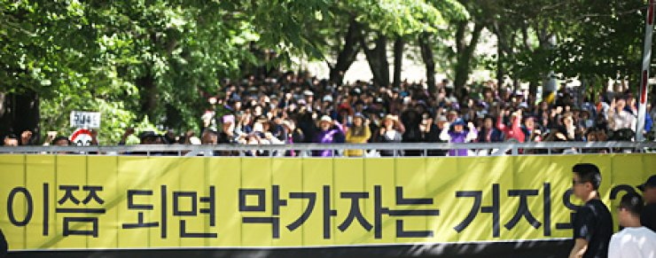 Followers of Yoo Byung-eun, the de facto owner of the sunken ferry Sewol and leader of the Salvation Sect, hold a rally inside Geumsuwon, the sect's stronghold, in Anseong, Gyeonggi Province, Monday, to denounce the prosecution's ongoing investigation of Yoo. The religious group said they will provide 500 million won to anyone who 'uncovers the truth behind the ferry disaster' in response to the prosecution's increase of a reward for assistance in the apprehension of Yoo and his eldest son to 500 million won a day earlier. / Yonhap