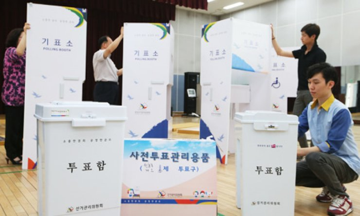 Officials from the Central Election Management Committee prepare for early voting ahead of the June 4 local elections at the Yongsan Culture Center in Seoul, Thursday. The early voting is aimed at those who cannot vote on the actual election day, and will take place for two days beginning today. / Yonhap