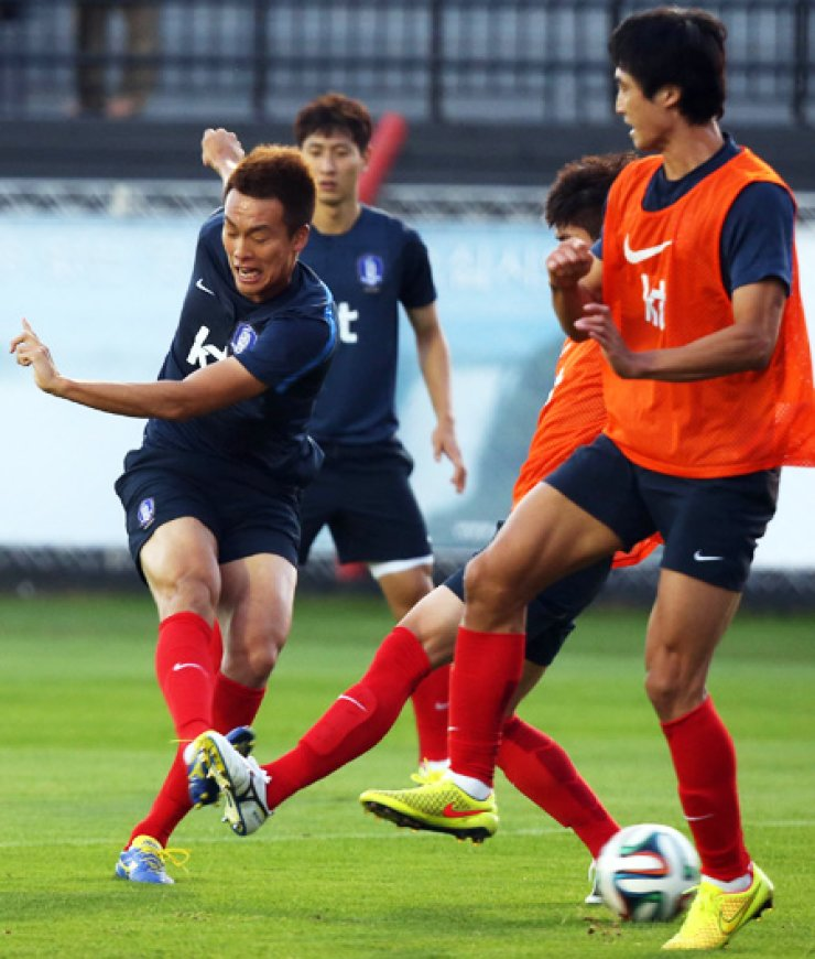 Striker Kim Shin-wook, left, unleashes a right-footed shot during a training session at the Korean team's base camp in Foz do Iguacu, Brazil, Thursday (KST), a day after its 1-1 draw with Russia in their opener in the World Cup. Kim and defensive back Kwak Tae-hwi, who missed the first match, are expected to play an important role in the next game against Algeria, Monday. / Yonhap