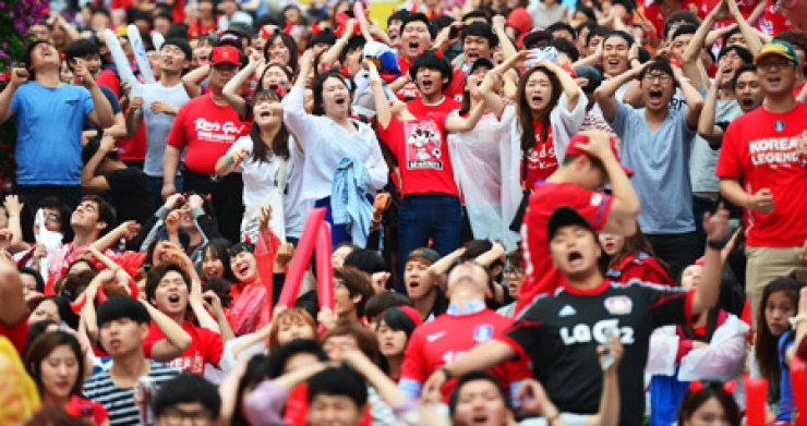 Football fans react after the Korean team missed an opportunity to score during the match against Algeria that was broadcast live at Gwanghwamun Square, central Seoul, Monday. Korea lost 2-4./ Korea Times photo by Shim Hyun-chul