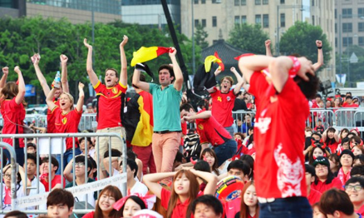 Korean football fans stand in disbelief after hen Belgium scored a goal against Korea, while Belgian fans shouted with joy as they watched the match between the two nations being broadcast at Gwanghwamun Square in central Seoul, early Friday. / Korea Times photo by Shim Hyun-chul