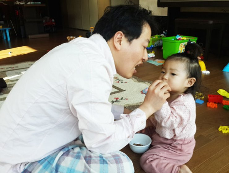 Suh Myong-hoon carries his two children on his back in this photo taken at his home in Seoul in December last year. He has hosted public campaigns for nearly one year to promote the importance of paternity leave in lifting the birthrate. / Courtesy of Suh Myong-hoon
