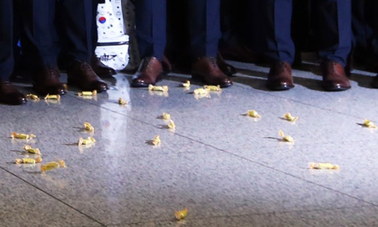 Wrapped yeot (Korean toffee) candies are scattered around the feet of Korean footballers who arrived at Incheon International Airport, Monday, after an early exit from the World Cup. A fan (unseen) threw the candies to express anger over their poor performances in Brazil. / Yonhap