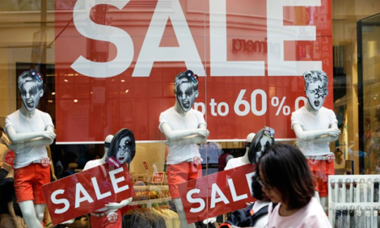 A woman walks by sale signs at a shopping district, Seoul, Thursday. The government unveiled stimulus plans after the shock of a deadly ferry sinking slowed economic growth to the lowest level in three quarters./ AP-Yonhap