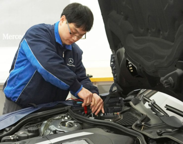 A mechanic replaces car parts at a Mercedes-Benz service center in this file photo. / Korea Times