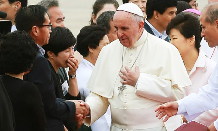 Pope Francis shakes hands with bereaved families of Sewol ferry victims upon his arrival at Seoul Airport in Seongnam, Thursday. / Yonhap