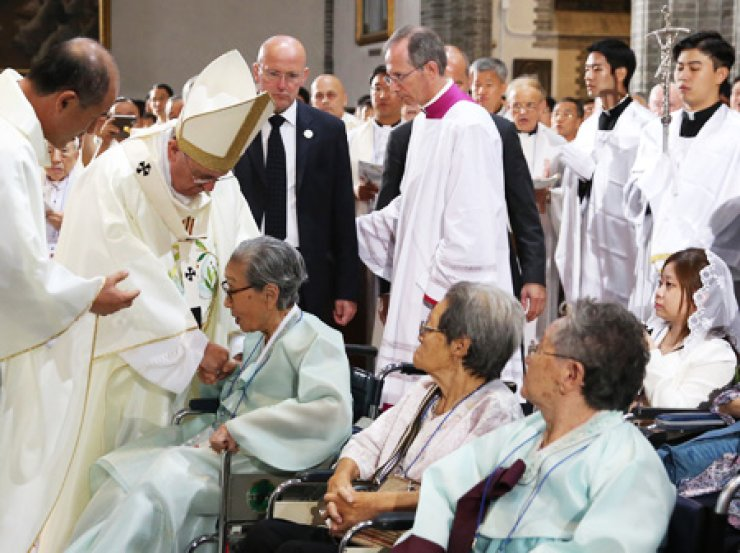 Pope Francis greets surviving victims of Japanese military sexual slavery prior to celebrating Mass at Seoul's Myeongdong Cathedral, Monday. The purpose of the Mass was to promote peace and reconciliation./ Korea Times photo by Hong In-ki