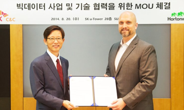 Lee Byung-song, left, a senior executive at SK C&C, poses with Jeff Markham, technical director handling Hortonworks' Asia-Pacific region, after the two companies signed a memorandum of understanding to collaborate over big data business. The signing was held in SK's main office in Seoul, Wednesday./ Courtesy of SK C&C