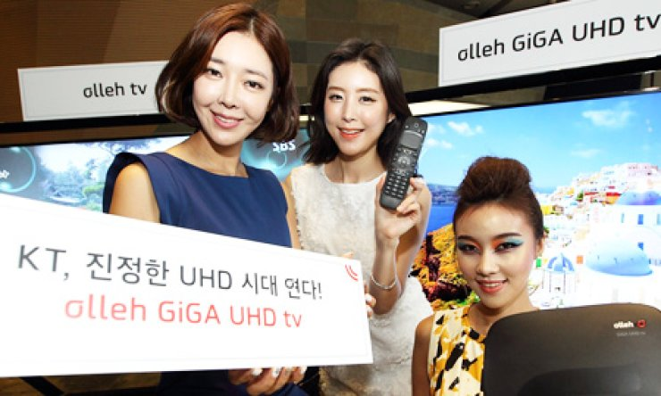 Models present a placard that reads; 'KT opens a new chapter in UHD TV era' during an event that celebrates the starts of its UHD TV service for the first time in the industry, Monday. / Courtesy of KT