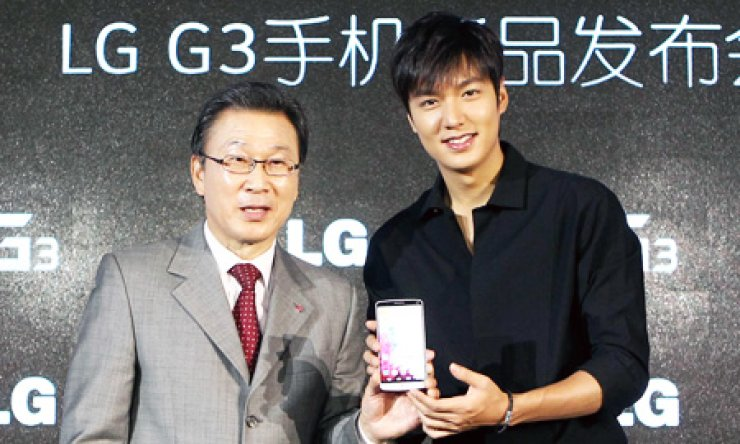 LG Electronics China President Shin Mum-beom, left, holds an LG G3 smartphone with Lee Min-ho, a Korean actor and an ambassador for LG mobile devices, during a launch event for the product for China at the Westin Hotel, Beijing, Aug. 8. / Korea Times file