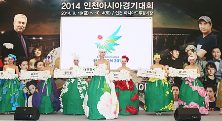 Models pose in modernized traditional clothes, made for the opening ceremony of the 2014 Incheon Asian Games, during a news conference at the National Museum of Modern and Contemporary Art in central Seoul, Wednesday. The organizing committee said the opening ceremony would be one of the highlights of the Asiad, led by the nation's veteran director Im Kwon-taek and produced by popular film director Jang Jin. Other distinguished artists will also be there, such as 'pansori' (Korean opera) master Ahn Sook-seon, violinist Richard Yongjae O'Neill and cellist Song Young-hoon. / Yonhap
