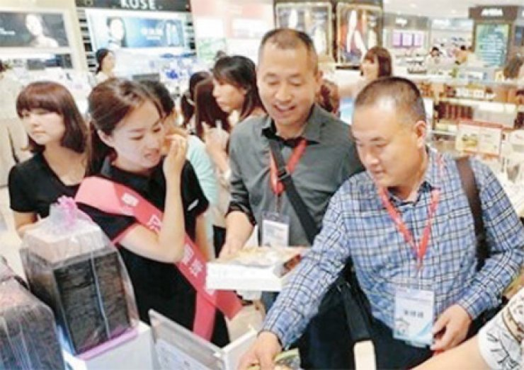 Chinese tourists shop at a duty-free shop in Seoul in this file photo./ Korea Times file