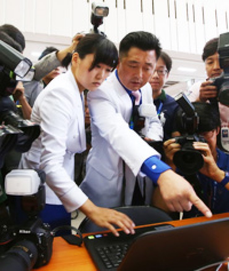A North Korean reporter points to a laptop computer in the Asian Games press center in Yeonsu-gu, Incheon, Friday, after it was blocked from accessing a North Korean website. Due to South Korea's National Security Law, the reporters have to send their reports to Pyongyang via fax machine. / Yonhap