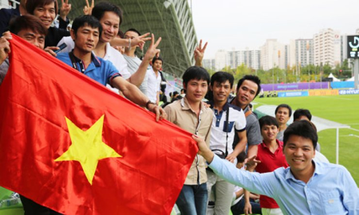 Vietnamese fans hold their country's national flag during an Incheon Asian Games women's football preliminary match between North Korea and Vietnam at Namdong Asiad Rugby Field in Nam-dong, Incheon, Tuesday./ Courtesy of Kwak Ji-hyun of Baedari photo gallery