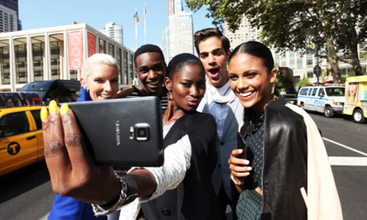 Models take a picture using Samsung Electronics' Galaxy Note 4 phablet during the New York Fashion Week, in New York, early this month. Samsung plans to promote the latest device in China to offset concerns over margin profitability due to the rise of budget Chinese smartphone vendors. / Korea Times file