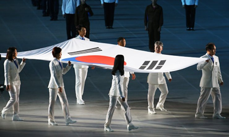 Jasmine Lee, left, carries the South Korean national flag with seven other flag bearers during the Incheon Asian Games' opening ceremony at the Incheon Asiad Main Stadium in Yeonhi-dong, Friday. Other bearers included golf star Pak Se-ri, mountain climber Um Hong-gil, marathoner Kim Bong-joo and three-time Asiad gold medalist Lim Chun-ae. The Philippine-born Lee is the country's first naturalized Korean to be elected as a lawmaker. / Yonhap