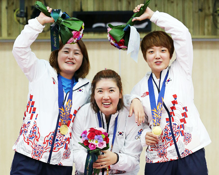 South Korea's Jeong Gyeong-mi, left, smiles as she holds her gold medal, standing next to silver medalist North Korea's Sol Kyong during the medal ceremony for the women's under-78 kg judo gold medal contest at the 17th Asian Games in Incheon, Monday. / AP-Yonhap