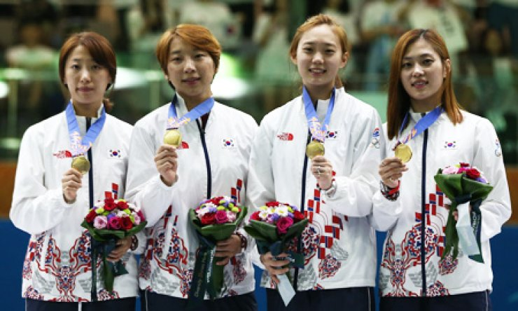 Korean female fencers show off their gold medals during an award ceremony at the Goyang Gymnasium, Gyeonggi Province, Tuesday, after they defeated their Chinese opponents in the final of the women's team sabre fencing. From left are Hwang Seon-a, Lee Ra-jin, Yoon Ji-su and Kim Ji-yeon. / Yonhap