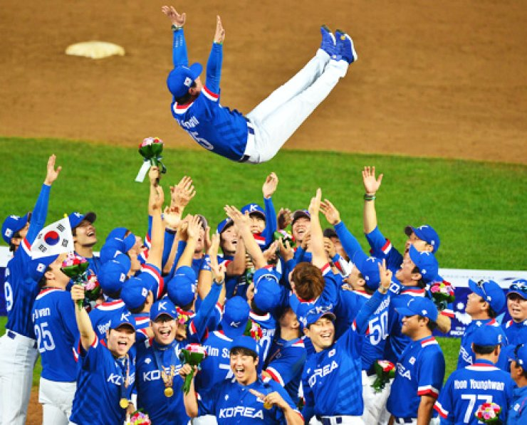 Members of South Korea's national baseball team toss their head coach, Ryu Joong-il, in the air to celebrate their 6-3 victory over Chinese Taipei in the final at the Munhak Stadium in Incheon, Sunday. / Korea Times photo by Shim Hyun-chul