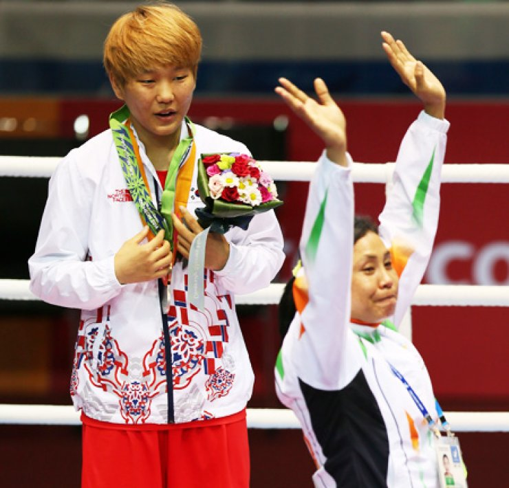 South Korean boxing silver medalist Park Jin-a reacts after Indian boxer Sarita Devi refused her bronze medal and instead hung it around Park's neck during a medal ceremony at the Seonhak Gymnasium, Wednesday. / Yonhap
