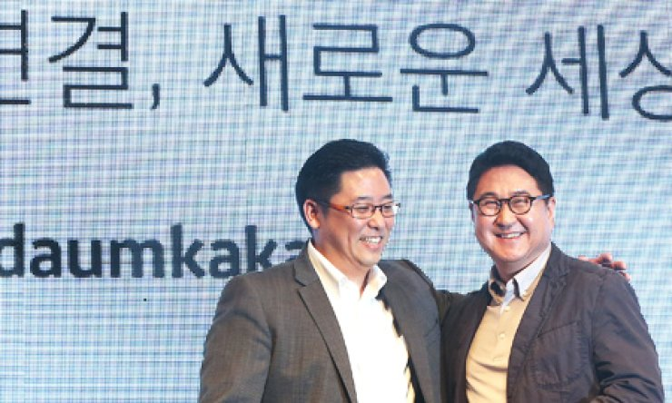 Choi Sae-hoon, left, and Lee Sir-goo, co-CEOs of Daumkakao, pose during a media briefing on the announcement of the merger between Daum Communications and Kakao at the Westin Chosun Hotel in Seoul, Wednesday. / Yonhap