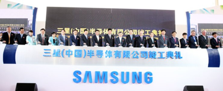 Samsung Electronics' Vice Chairman Kwon Oh-hyun, eleventh from left, poses with senior Chinese politicians and other officials at an event to celebrate the operation of the company's mega chip-manufacturing plant in Xian, western China, in this file photo taken in May. Samsung is increasing investment in semiconductor and display plants in China to cut expenditure on labor and logistics. / Korea Times file