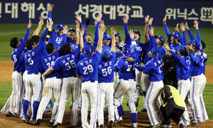 The Samsung Lions' players cheer after winning the 2014 Korea Baseball Organization (KBO) Series at Jamsil Stadium in southern Seoul, Tuesday. The Lions routed the Nexen Heroes 11-1 in game 6 of the series to become the champions for the fourth straight year. / Yonhap
