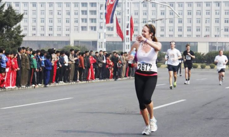 A runner waves her hand to North Korean locals during the 2014 Pyongyang Marathon, which was opened to foreign amateurs for the first time in April./ Courtesy of Young Pioneer Tours