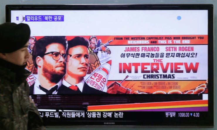 A soldier walks past a TV showing an advertisement for Sony Pictures' 'The Interview' at Seoul Station, Monday. / AP-Yonhap
