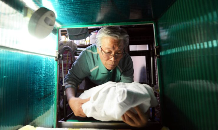 Pastor Lee Jong-rak demonstrates how a 'baby box' works. Korea Times file