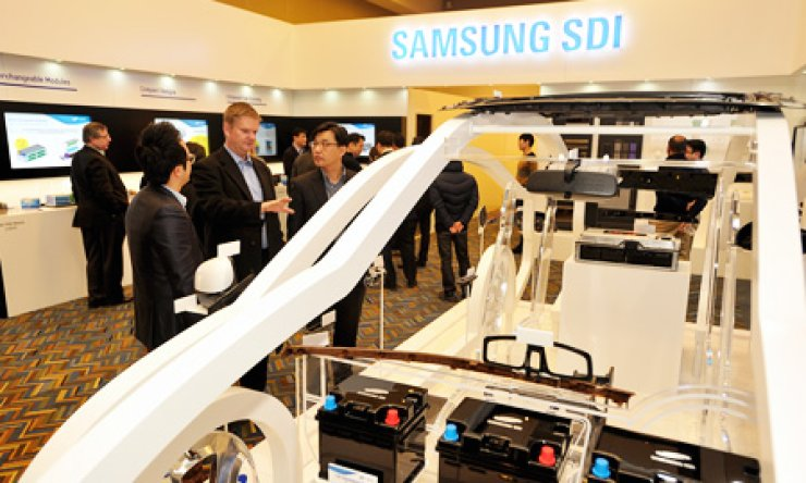 A Samsung SDI employee gives a briefing about the company's electric car battery cells and car material products to visitors at the company's exhibition booth during the 2015 North American International Auto Show at the Cobo Center in Detroit, Michigan, Monday. / Courtesy of Samsung SDI