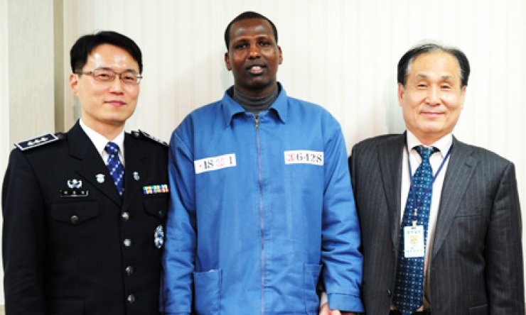 Seok Hae-kyun, right, a former captain of the Samho Jewelry that was hijacked by Somali pirates on Jan. 15, 2011 in waters off the Omani coast, poses with Arai Mahomed, center, who shot him during a Navy rescue operation five days later, at a prison in Daejeon on Jan. 14. At left is a prison officer, who interpreted for them./ Yonhap
