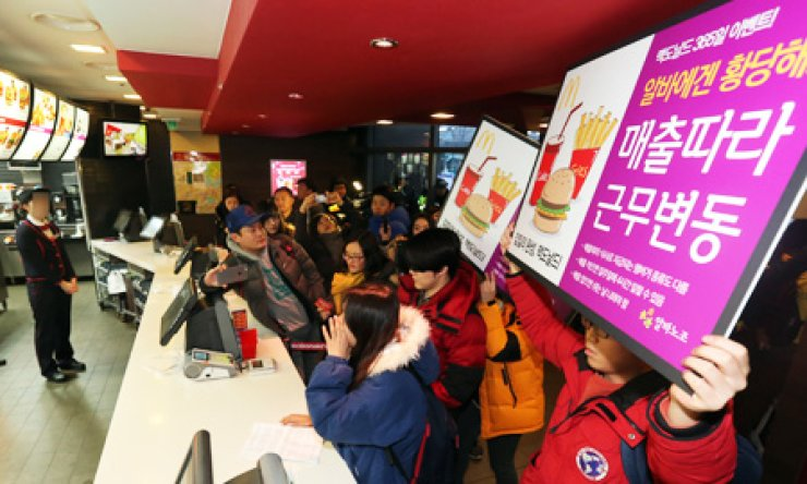 A group of activists protest inside a McDonald's outlet in Sinchon, Seoul, Saturday, against what they claim is the firm's exploitation of part-time workers. / Yonhap