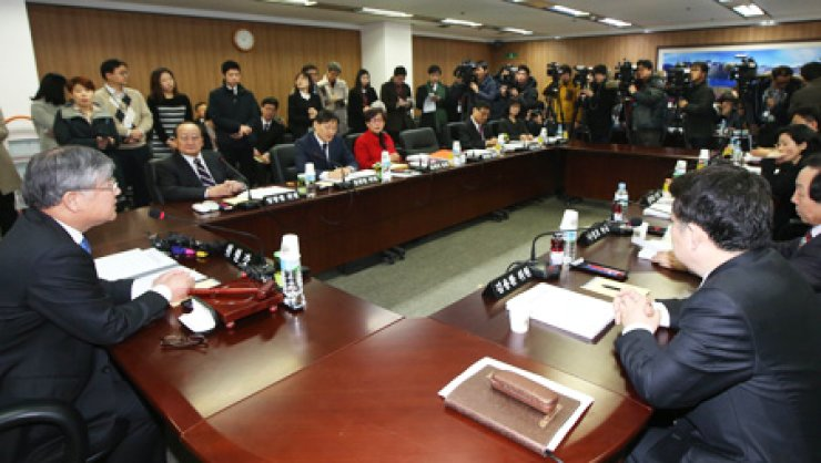 Lee Un-chul, left, chairman of the Nuclear Safety and Security Commission (NSSC), speaks to decision-making panelists before starting a meeting on the fate of the country's oldest nuclear reactor, the Wolsong-1, at the NSSC in downtown Seoul, Thursday. They failed to reach a consensus on the issue and decided to have a third round of talks on Feb. 26. / Yonhap