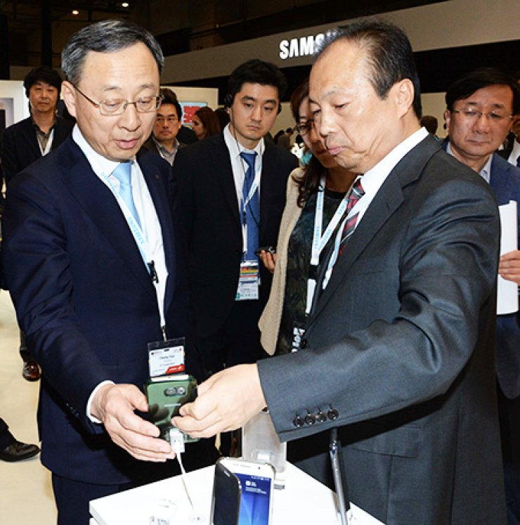 KT Chairman Hwang Chang-gyu, left, listens to an introduction about Samsung Electronics' new Galaxy S6 smartphone alongside Samsung's mobile business division chief Shin Jong-kyun, right, during their visit to Samsung's exhibition booth at the Mobile World Congress in Barcelona, Spain, Tuesday. / Yonhap