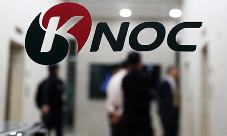 Korea National Oil Corp. workers stand outside their offices at the state-run company's headquarters in Ulsan, Wednesday, which are being searched by prosecutors. / Yonhap