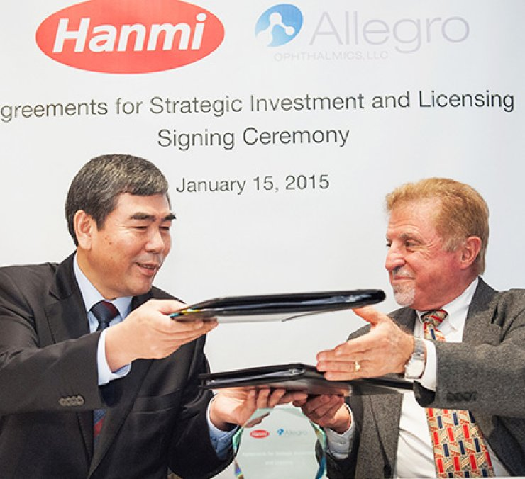 Hanmi Pharm CEO Lee Kwan-soon, left, exchanges a signed agreement with his counterpart from Allegro Ophthalmics, a U.S. tech startup, in San Francisco, in January. The two companies will make a joint investment and share each other's patented technologies to develop medicines for various eye diseases./ Courtesy of Hnami Pharm