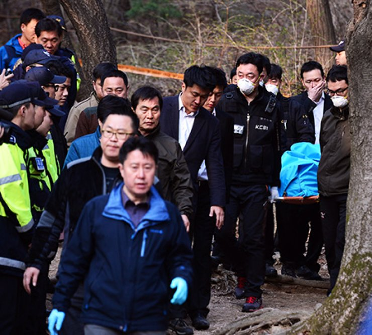 Police officers carry the body of former Keangnam Enterprise Chairman Sung Woan-jong down from a mountainside, Thursday. Sung is believed to have committed suicide by hanging himself from a tree on Mount Bukhan in northern Seoul the same day. / Korea Times Photo by Shim Hyun-chul