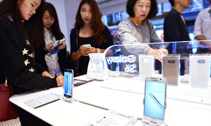 Customers look at the new Samsung Galaxy S6 and S6 Edge at a store in Sydney on Friday. Samsung said it expects its new flagship smartphone to shatter sales records and pull the company out of a recent profit slump that saw it lose ground to arch-rival Apple and cheaper Chinese smartphone makers. / AFP-Yonhap
