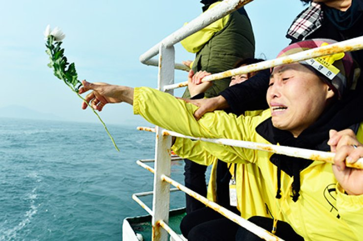 A relative of a Sewol victim throws a flower into the water during her visit to the site where the ferry sank near Jindo in South Jeolla Province, Wednesday, the eve of the first anniversary of the ferry disaster./ Korea Times photo by Shim Hyun-chul