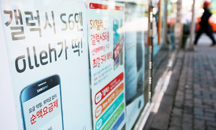 Posters promoting raised subsidies for those who buy Samsung Electronics' Galaxy S6 and S6 Edge are attached to a handset outlet in central Seoul, Monday. Local telecom companies increased the subsidies to attract more subscribers to the new Samsung smartphones a week after their release on April 10. / Yonhap