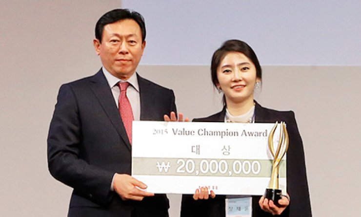 Lotte Group Chairman Shin Dong-bin, left, poses after giving the 'Value Champion Awards' to Jang Chae-yoon, an employee of its retail affiliate 7-Eleven, during the 2015 Lotte Human Resource Forum at Lotte Hotel in Jamsil, Seoul, Monday./ Courtesy of Lotte Group