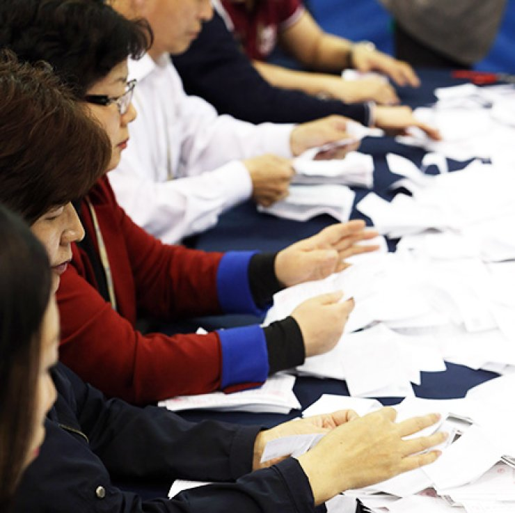 National Election Commission officials count ballots at Inheon Elementary School in Nakseongdae,  Seoul, Wednesday. / Yonhap