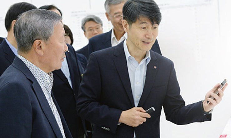 LG Chairman Koo Bon-moo, left, is briefed on the G4 smartphone by LG Electronics mobile chief Cho Juno during his tour of the company's research center in the Gasan Digital Complex, western Seoul, Wednesday. / Courtesy of LG