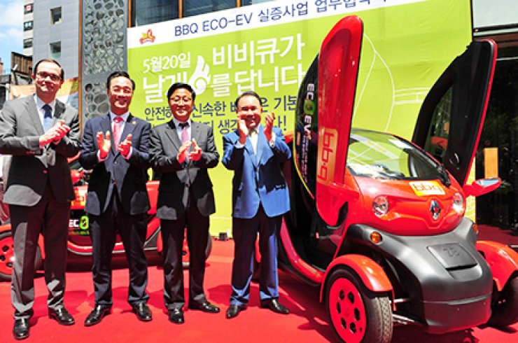 Yoon Hong-geun, right, chairman of the Genesis BBQ Group, poses with Renault Samsung Motors CEO Francois Provost, left, during a ceremony at BBQ's flagship store in downtown Seoul, Wednesday, to mark the chicken franchise's use of the automaker's electric vehicles for deliveries. / Courtesy of BBQ Genesis