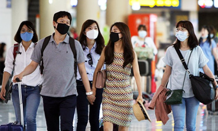Tourists to Jeju Island walk wearing masks at Jeju International Airport, Thursday, amid fears of Middle East Respiratory Syndrome. / Yonhap